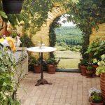 Poster de jardin en trompe-l'oeil : effet mur en pierre et vue sur la vallée ©Teunstuinposters.nl